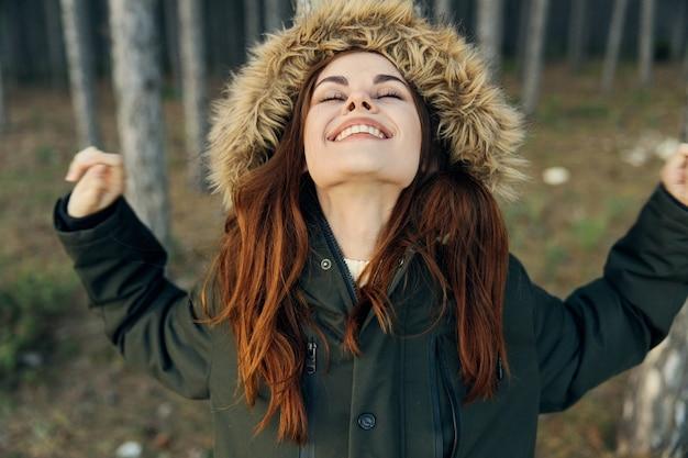 Frau mit geschlossenen augen in kapuzenjacke schaut oben frische luft freiheit lebensstil