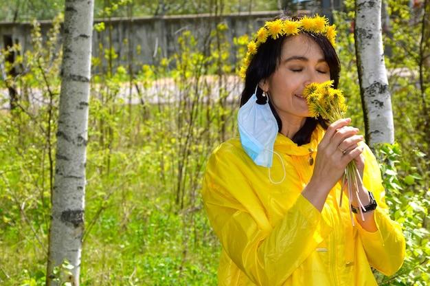 Frau mit geschlossenen augen und entfernter medizinischer maske, die löwenzahn riecht