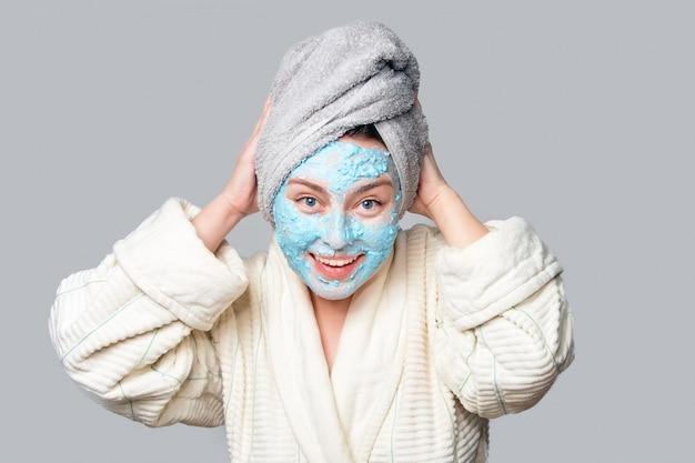 Frau mit gesichtslehmmaske am spa-salon oder zu hause, hautpflegethema. mädchen entfernt alginat kosmetische maske. gesichtsmaske, spa-schönheitsbehandlung mit kopierraum
