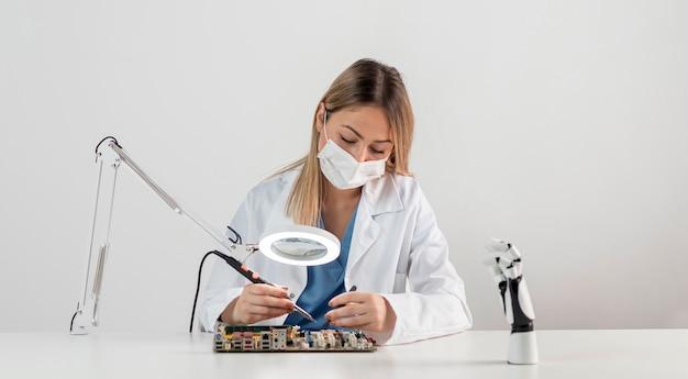 Frau mit gesichtsmaske, die am schreibtisch arbeitet
