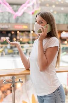 Frau mit gesichtsmaske, die am telefon im einkaufszentrum spricht