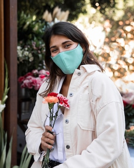 Frau mit gesichtsmaske, die draußen mit blumen aufwirft