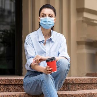 Frau mit gesichtsmaske, die eine tasse kaffee hält