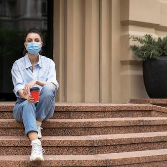 Frau mit gesichtsmaske, die eine tasse kaffee mit kopienraum hält