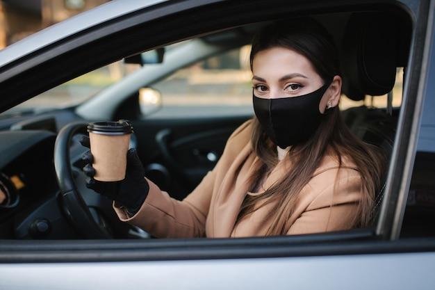Frau mit gesichtsmaske, die ihr auto mit tasse kaffee während der coronavirus-pandemie fährt,