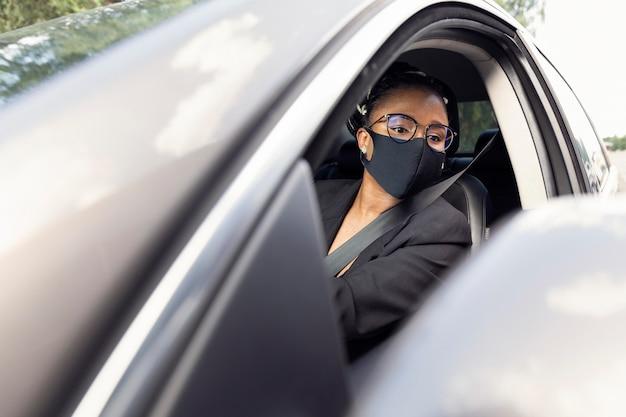 Frau mit gesichtsmaske, die in den spiegel schaut, während sie ihr auto fährt