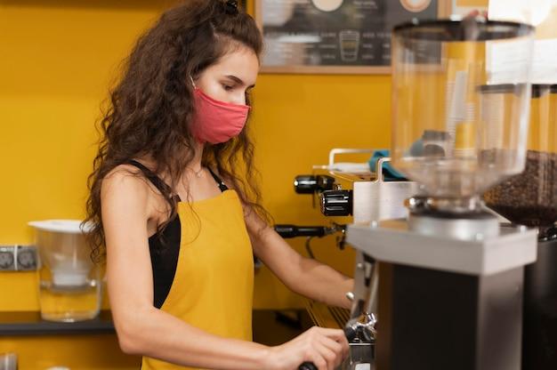 Frau mit gesichtsmaske, die in einem kaffeehaus arbeitet