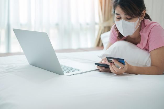 Frau mit gesichtsmaske, die kreditkarte hält und handy und laptop für online-einkäufe auf dem bett am morgen zu hause verwendet.