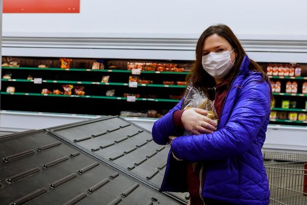 Frau mit gesichtsmaske, die letzten beutel der kartoffel am supermarkt mit leeren regalen hält.