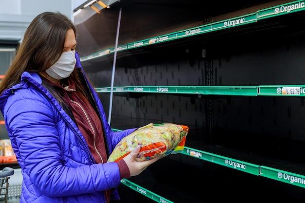 Frau mit gesichtsmaske, die letzten beutel des salats am supermarkt mit leeren regalen hält.