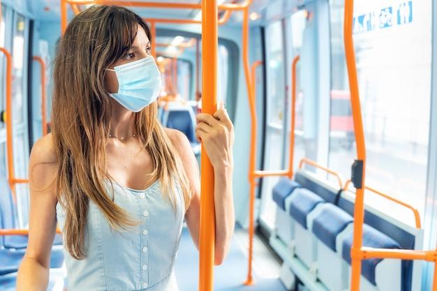 Frau mit gesichtsmaske, die mit der straßenbahn während des coronavirus-ausbruchs fährt. hochwertiges foto