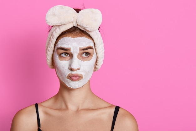 Frau mit gesichtsmaske, die mit nachdenklichem gesichtsausdruck beiseite schaut, lustiges haarband habend, das über rosa wand lokalisiert aufwirft. kopieren sie platz für werbung.