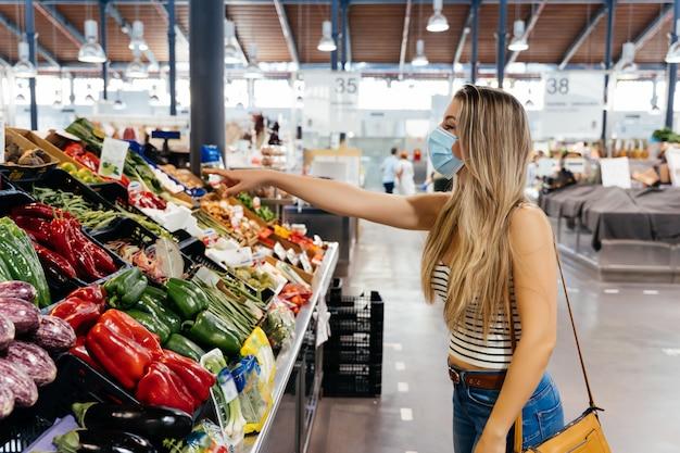 Frau mit gesichtsmaske, die obst und gemüse am zentralen stadtmarkt kauft