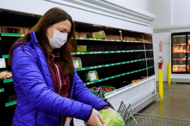 Frau mit gesichtsmaske, die salat am laden mit leeren regalen kauft.