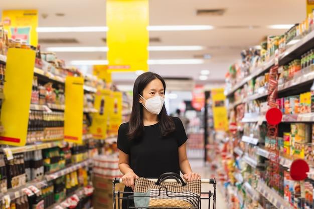 Frau mit gesichtsmaske, die während der coronavirus-quarantäne im supermarkt einkaufen