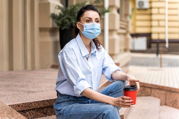 Frau mit gesichtsmaske hält eine tasse kaffee beim sitzen auf treppen