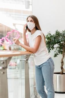 Frau mit gesichtsmaske im einkaufszentrum, die am telefon spricht