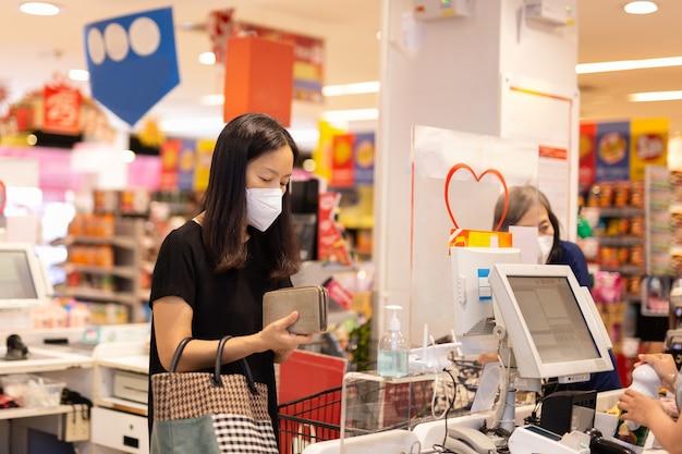 Frau mit gesichtsmaske-kasse an der kasse im lebensmittelgeschäft