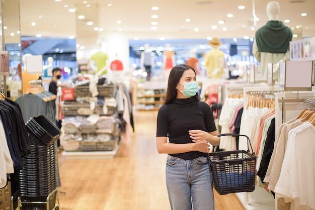 Frau mit gesichtsmaske kauft kleidung im einkaufszentrum ein