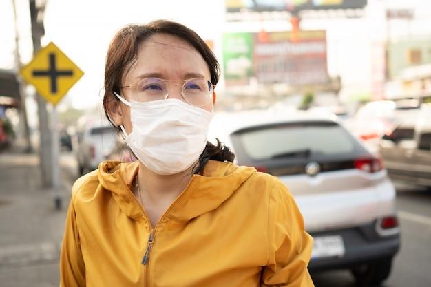 Frau mit gesichtsmaske schützt filter vor luftverschmutzung (pm2.5)