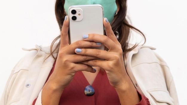 Frau mit gesichtsmaske unter verwendung des smartphones
