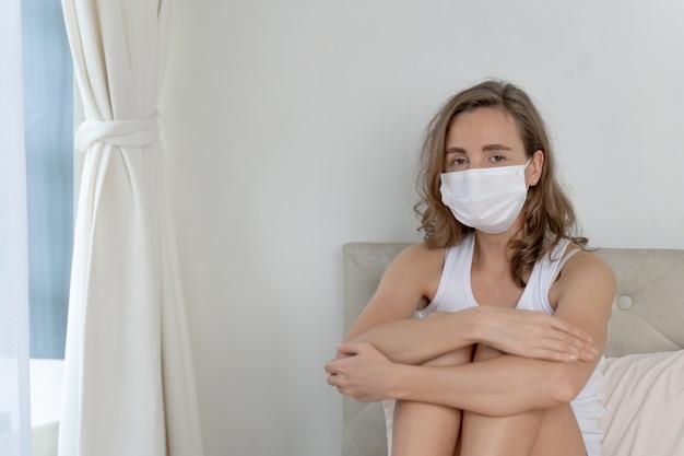 Frau mit gesichtsmaske zum schutz vor kopfschmerzen und husten wegen coronavirus covid-19 im quarantäneraum