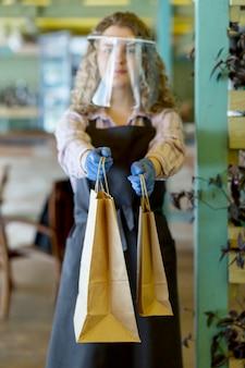 Frau mit gesichtsschutz bei kundenauftrag