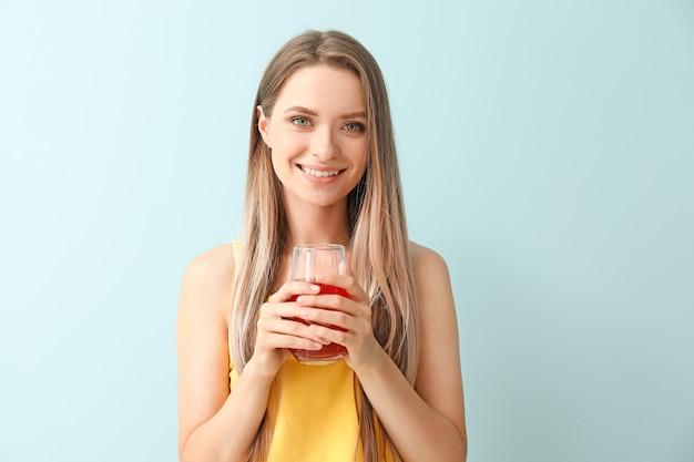 Frau mit gesundem saft auf blau. ernährungskonzept