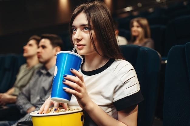 Frau mit getränk und popcorn, die im kino sitzen