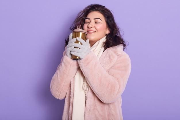 Frau mit gewelltem haar, das steht und von etwas träumt, während thermo-tasse tee oder kaffee hält und seinen geruch genießt