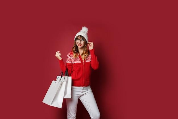 Frau mit gewellten haaren, die mit weißen einkaufstüten stehen