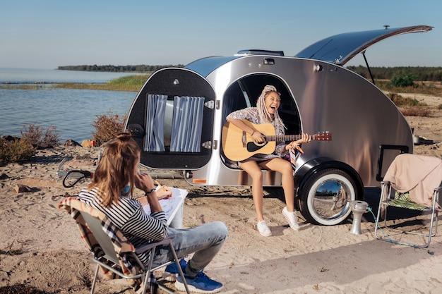 Frau mit gitarre. stilvolle frau mit weißen dreadlocks, die gitarre halten, während musik für ihren freund spielen