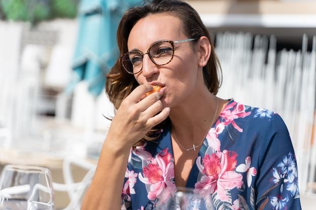 Frau mit gläsern, die ein stück sushi mit ihrer hand essen