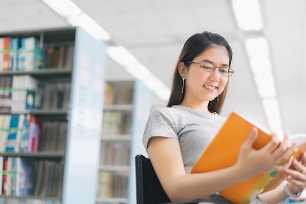Frau mit gläsern ein buch in der bibliothek lesend.