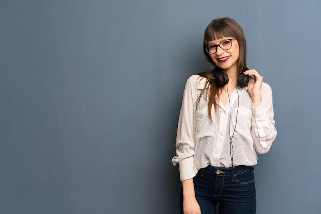 Frau mit gläsern über blauer wand mit kopfhörern