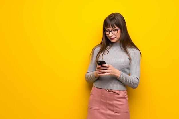 Frau mit gläsern über der gelben wand, die eine mitteilung mit dem mobile sendet