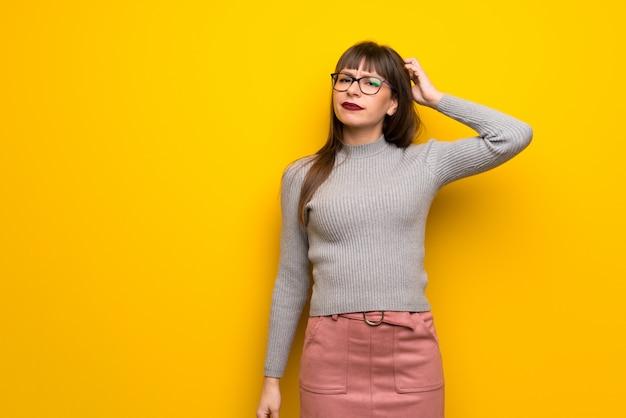 Frau mit gläsern über der gelben wand, die zweifel beim verkratzen des kopfes hat