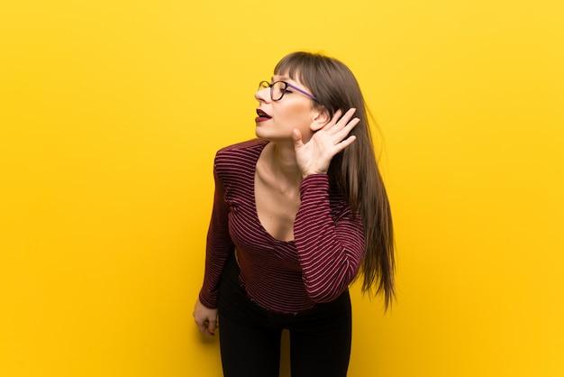 Frau mit gläsern über gelber wand hörend auf etwas, indem sie hand auf das ohr setzen