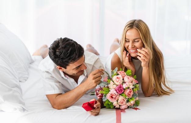 Frau mit glücklicher lächelnder reaktion nach dem liebhaber, der um bittet, heiraten mit ring auf bett