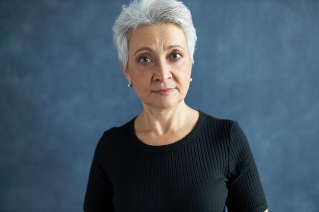 Frau mit grauem haar im lässigen schwarzen t-shirt überrascht