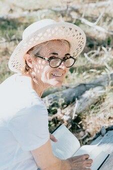 Frau mit grauen haaren am strand während eines super sonnigen tages seniorenfreiheitskonzept kopie raum sonne