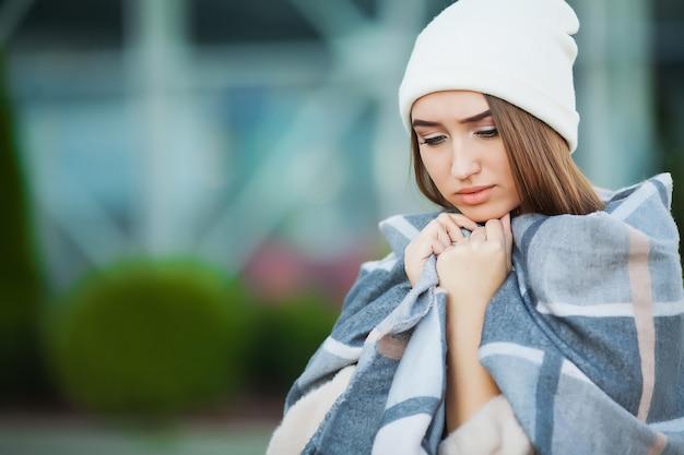 Frau mit grippe im freien gekleidet in mütze