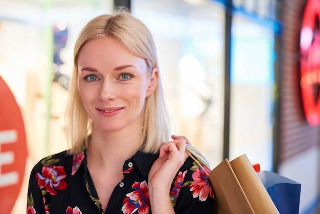Frau mit großem lächeln im gesicht nach dem großen einkaufen