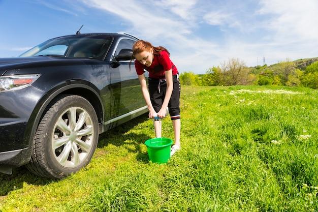 Frau mit grünem eimer, die seifenschwamm auswringt und schwarzes luxusfahrzeug auf der grünen wiese an einem sonnigen tag mit blauem himmel wäscht?