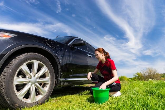 Frau mit grünem eimer wäscht schwarzes luxusfahrzeug mit seifenschwamm im grünen feld an einem hellen sonnigen tag mit blauem himmel