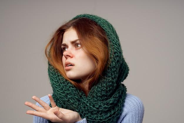 Frau mit grünem schal auf ihrem kopf gestikuliert mit händen auf grauen hintergrundgesundheitsproblemen. hochwertiges foto