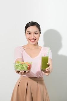 Frau mit grünen detox-smoothies, salat in glasschüssel isoliert. richtige ernährung, vegetarisches essen, gesunder lebensstil, diätkonzept. bereich zum kopieren von platz