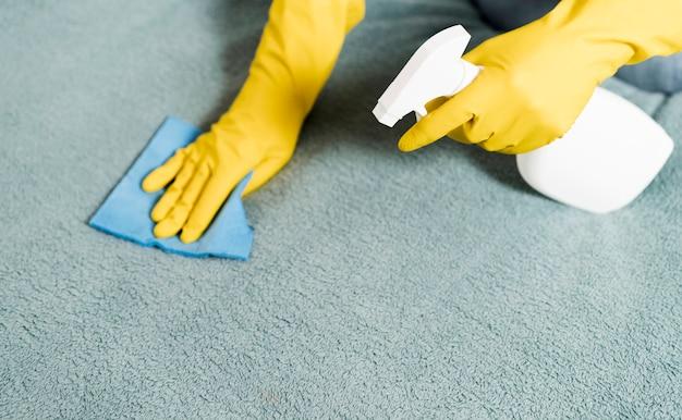 Frau mit gummihandschuhen, die den teppich reinigen