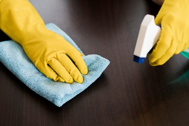 Frau mit gummihandschuhen, die den tisch reinigen