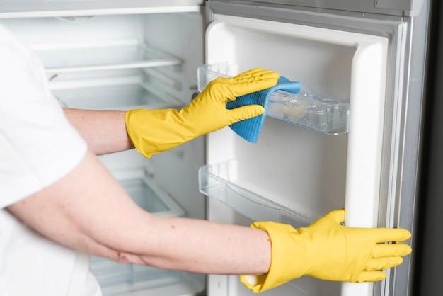 Frau mit gummihandschuhen, die kühlschrank reinigen